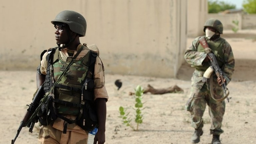 Nigerian soldiers patrol in the north of Borno state on June 5, 2013 near a deserted Boko Haram camp. Nigeria's military has banned the use of satellite phones in much of the restive northeast after cutting mobile phone service, further isolating the area after a series of fresh attacks.