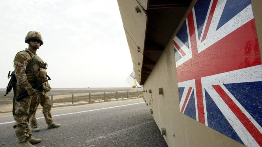 British soldiers keep watch as a tank drives by in Basra, southern Iraq, on December 16, 2007. Relatives of British soldiers killed while fighting in Iraq can sue the government for negligence and claim damages under human rights law, the Supreme Court in London ruled on Wednesday.