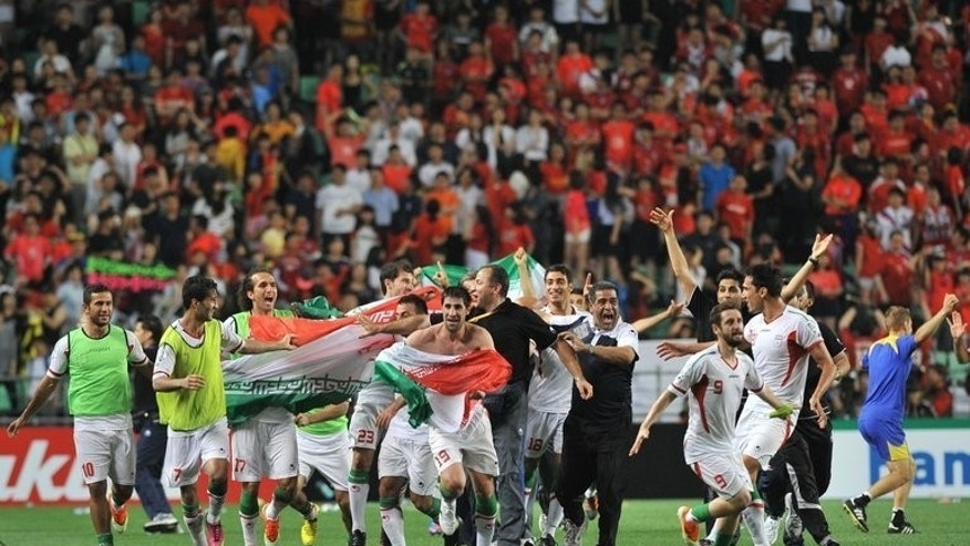 Iran players celebrate victory over South Korea in a World Cup qualifier in Ulsan, Korea, on Tuesday. South Korean media blamed Iran Wednesday for angry scenes at a tense World Cup qualifier which ended with fans pelting debris on to the pitch and the visiting coach under fire for a rude gesture.