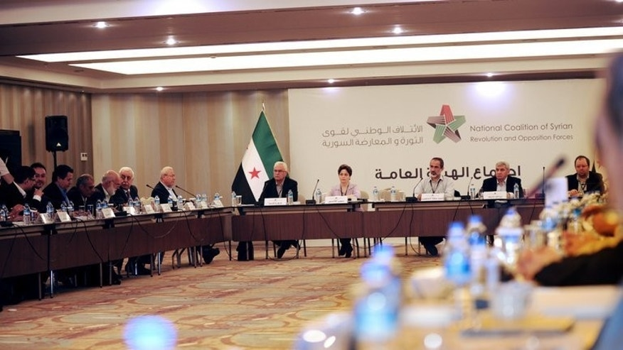 Members of Syria's opposition National Coalition attend a meeting in Istanbul last month. Syria's main opposition bloc said Wednesday it will fight on to topple President Bashar al-Assad, and that any political solution to the conflict must lead to the fall of the regime.