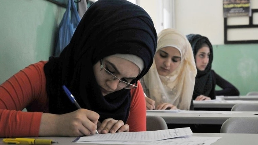 Syrian students take exams in the Lebanese town of Tripoli last week. Forced by Syria's war to sit her secondary school diploma exam in northern Lebanon, Riham Othman, 19, bursts into tears, fearing the Lebanese authorities will never recognise the test results.
