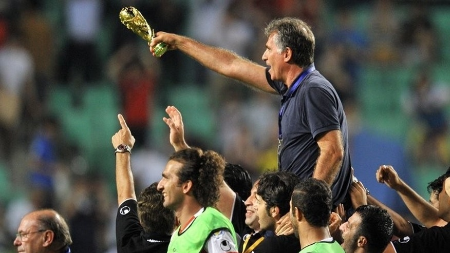 Iran head coach Carlos Queiroz holds a mock trophy after his side defeated South Korea in Ulsan on June 18, 2013. South Korea accused Queiroz of making an obscene hand gesture at his rival Choi Kang-Hee, and said they expected a FIFA investigation.