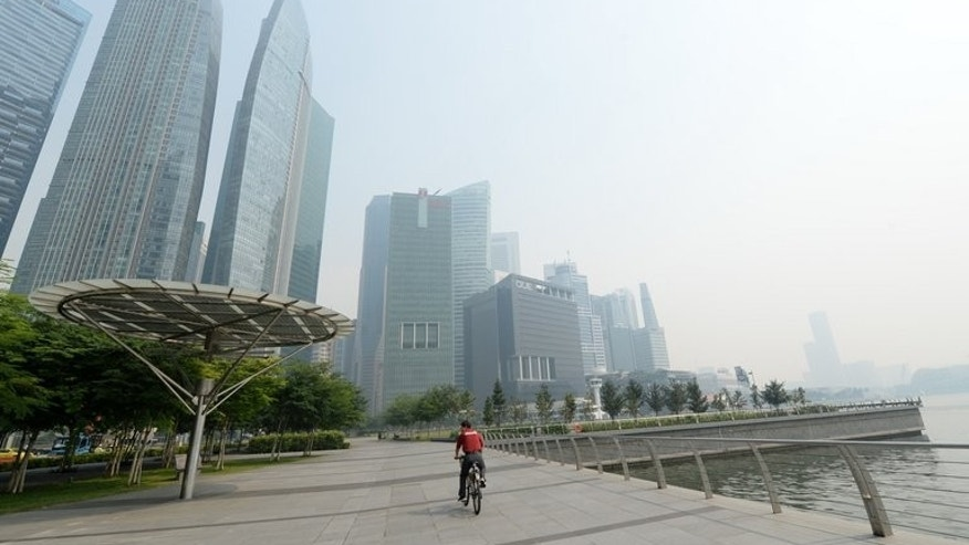 A cyclist rides along the pier in front of buildings blanketed by haze in Singapore on June 19, 2013. Singapore's smog problem from forest fires in Indonesia worsened Wednesday as air pollutant levels reached a 16-year high.