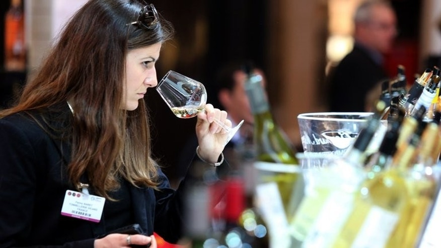 "A woman tastes wine during the Vinexpo trade fair in Bordeaux, southwestern France, on June 17, 2013. For years the Chinese have been buying up wine from Europe, but with domestic wine production predicted to overtake Australia and Chile by next year, Tiana Wu is hoping European drinkers are ready to be tempted by a glass of her ""Yunnan Red""."
