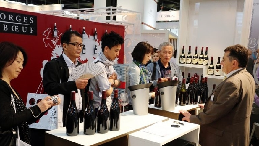 "Asian buyers speak to a French wine producer at the Vinexpo trade fair in Bordeaux, southwestern France, June 17, 2013. For years the Chinese have been buying up wine from Europe, but with domestic wine production predicted to overtake Australia and Chile by next year, Tiana Wu is hoping European drinkers are ready to be tempted by a glass of her ""Yunnan Red""."
