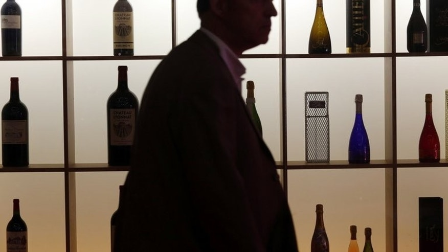 "A man walks past a wall of wine bottles at the Vinexpo trade fair in Bordeaux, southwestern France, on June 17, 2013. For years the Chinese have been buying up wine from Europe, but with domestic wine production predicted to overtake Australia and Chile by next year, Tiana Wu is hoping European drinkers are ready to be tempted by a glass of her ""Yunnan Red""."