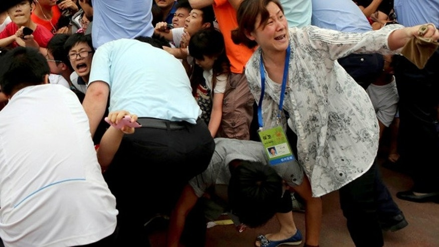 June 20, 2013: A crowd reacts during a stampede by fans of David Beckham at a university in Shanghai on Thursday.  Fans eager to the see the soccer superstar stormed a police cordon Thursday in a stampede at a Shanghai university that injured seven people including five security personnel.