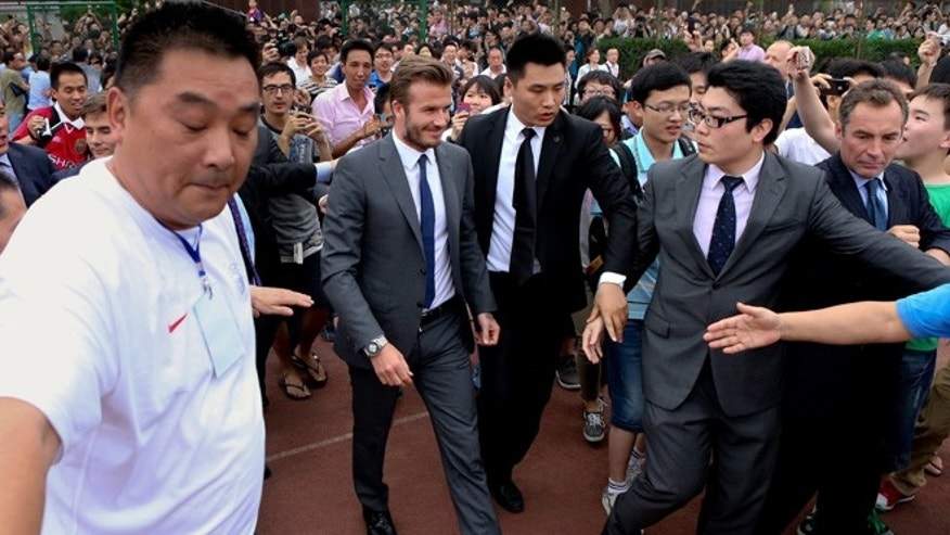 June 20, 2013: David Beckham walks to meet his fans before a stampede caused by fans storming a security cordon in a university in Shanghai. Fans eager to see the soccer superstar stormed a police cordon in a stampede that injured seven people including five security personnel.