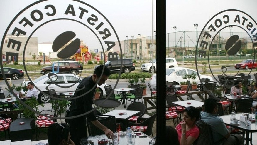 Iraqis sit at a coffee shop in the northern city of Arbil on June 20, 2013. In Arbil, crowded cafes overflow onto sidewalks, customers pack out restaurants with no fear of attack and, perhaps most importantly for the three-province region's future prospects, foreign investors appear keen to plant their flag.
