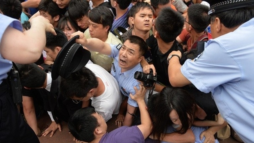 People fall in a stampede during football superstar David Beckham's visit to Tonji University in Shanghai on June 20, 2013. Beckham on Friday sent his love to people hurt in a stampede at a Shanghai event, as fans praised him despite the incident.
