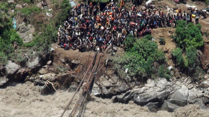 June 21, 2013 - Indo-Tibetan Border Police personnel help stranded pilgrims on a makeshift bridge cross a stream of gushing floodwater at Govind Ghati, in northern Indian state of Uttarakhand, India.