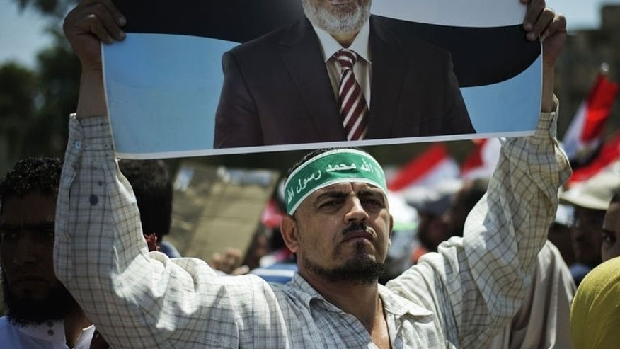 Egyptian Islamist groups led by the ruling Muslim Brotherhood take part in a demonstration to mark the upcoming one year anniversary since President Mohamed Morsi (portrait) was elected, on June 21, 2013 in Cairo.