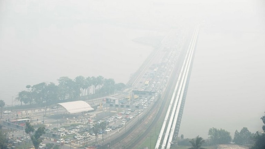 A general view of the causeway from Singapore to Johor Bahru (background), obscured by thick haze, on June 21, 2013. Singapore's smog index hit the critical 400 level, making it potentially life-threatening to the ill and elderly people, according to a government monitoring site.