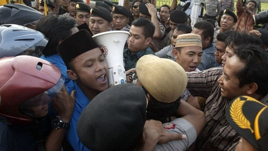 Demonstrators tussle with police during a protest against the impending oil price increase in Surabaya city in eastern Java island on June 21, 2013. Indonesia on Friday announced the first hike in fuel prices since 2008 despite violent protests against the unpopular measure, as Southeast Asia's top economy seeks to reduce crippling subsidies.