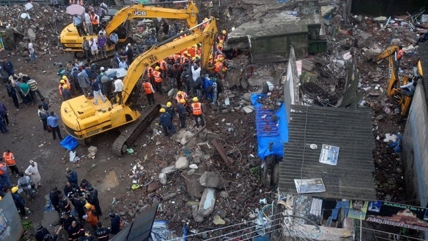 Indian rescue workers gather at the site of a apartment block collapse in Mumbra, on the outskirts of Mumbai on June 21, 2013. The building collapse killed at least 10 people and trapped more in the debris.