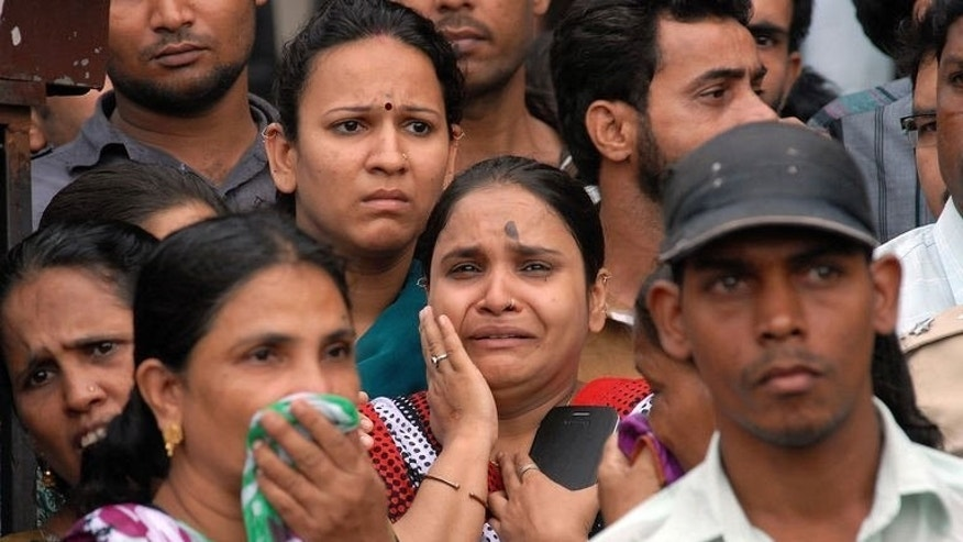 People await news of their loved ones after an apartment collapse in Mumbra, on the outskirts of Mumbai, June 21, 2013. The building collapse killed at least 10 people and trapped more in the debris.