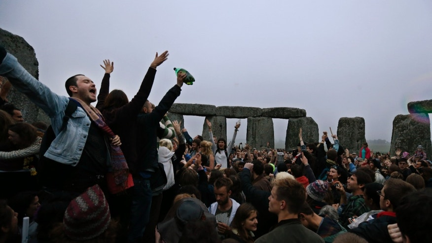 June 21, 2013 - People dance and raise their hands in celebration during the summer solstice shortly after 04.52 am at the prehistoric Stonehenge monument, near Salisbury, England, Friday. Following an annual all-night party, thousands of new agers and neo-pagans waited at the ancient stone circle Stonehenge for the sun to come up, but cloudy skies prevented them. They danced and whooped in delight .