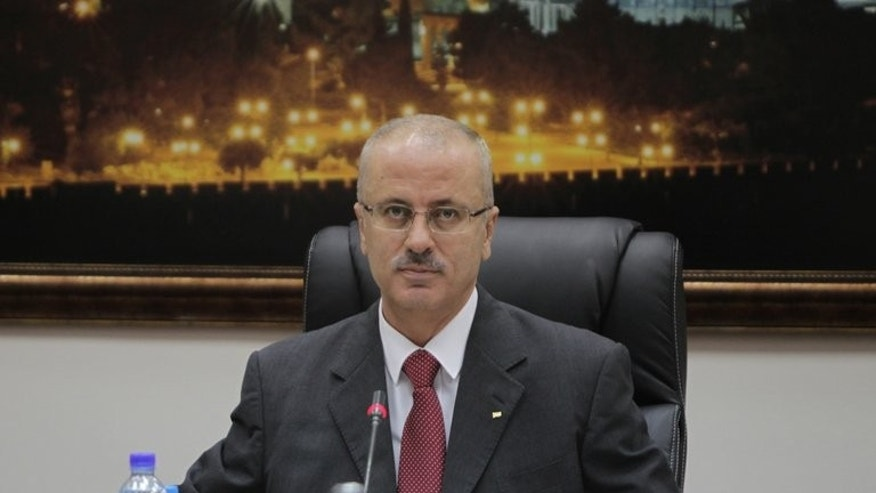 Palestinian Prime Minister Rami Hamdallah chairs the first working meeting of the new Palestinian government in the West Bank town of Ramallah on June 11, 2013. Hamdallah on Friday withdrew an offer to quit a day after presenting it to president Mahmud Abbas, a high-ranking government official said.