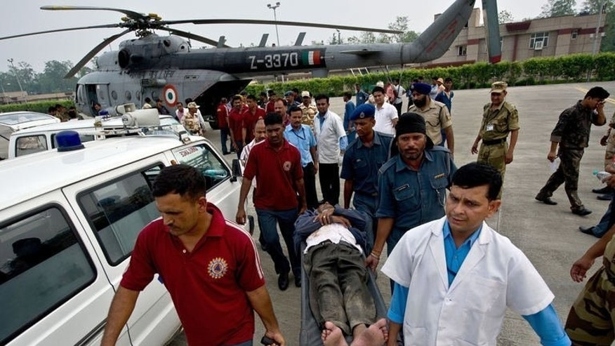 An Indian pilgrim, evacuated from flood-hit areas by the Indian Air Force (IAF), is transported by medics at the Jolly Grant Airport in Dehradun, Uttarakhand on June 21, 2013. Rescuers have recovered scores of bodies from the Ganges river in northern India, as the death toll from flash floods and landslides nears 600, with thousands still stranded or missing.