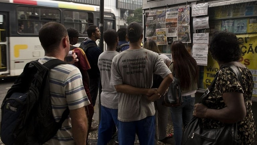 People read the front pages of newspapers at a newstands on Presidente Vargas avenue in downtown Rio de Janeiro, Brazil on June 21, 2013.