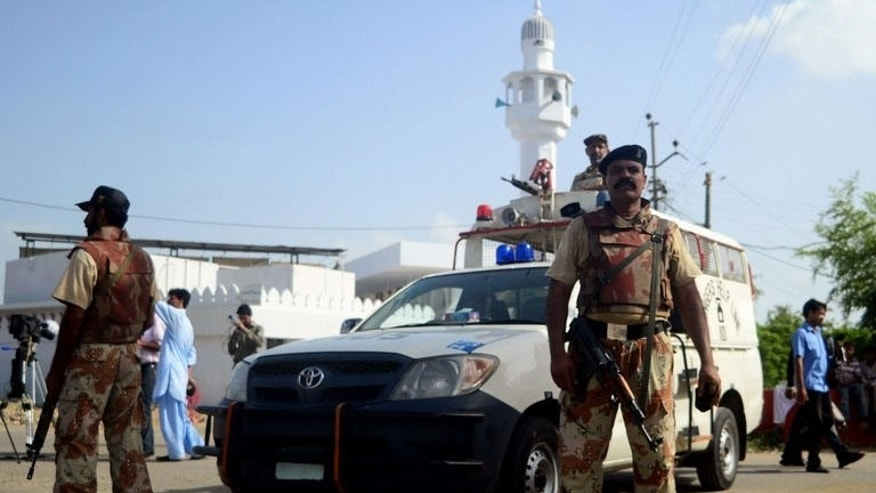 Pakistani paramilitary soldiers stand guard outside the mosque where gunmen shot dead Pakistani lawmaker Sajid Qureshi in Karachi on June 21, 2013.