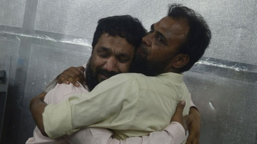 Relatives of Sajid Qureshi, a Pakistani lawmaker who was killed by gunmen, mourn at a morgue in Karachi on June 21, 2013.