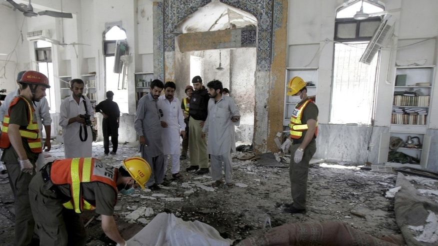 June 21, 2013 - Pakistani volunteers cover a lifeless body  following a suicide bombing at a Shiite mosque in Peshawar, Pakistan.