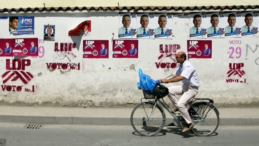 A man rides past electoral posters in Tirana on June 22, 2013. Albanians go to the polls on Sunday for a crucial vote that could determine whether one of Europe's poorest countries has a chance of joining the European Union in the foreseeable future.