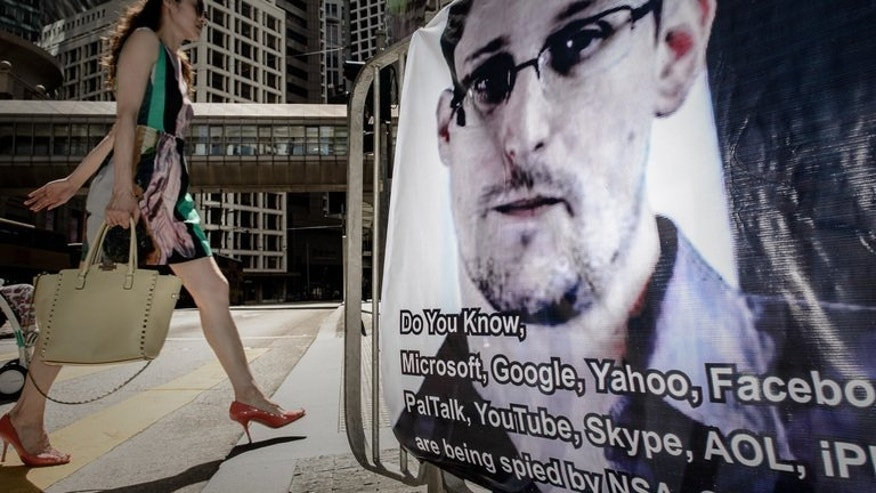 A woman walks past a banner displayed in support of former US spy Edward Snowden in Hong Kong on June 18, 2013. Britain's electronic eavesdropping agency has gained secret access to fibre-optic cables carrying global Internet traffic and telephone calls, according to a newspaper report citing documents disclosed by Snowden.