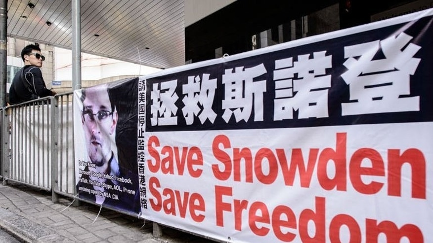 A man stands next to a banner in support of rogue intelligence technician Edward Snowden in Hong Kong on June 18, 2013. Britain's electronic eavesdropping agency has gained secret access to fibre-optic cables carrying global Internet traffic and telephone calls, according to a newspaper report citing documents disclosed by Snowden.