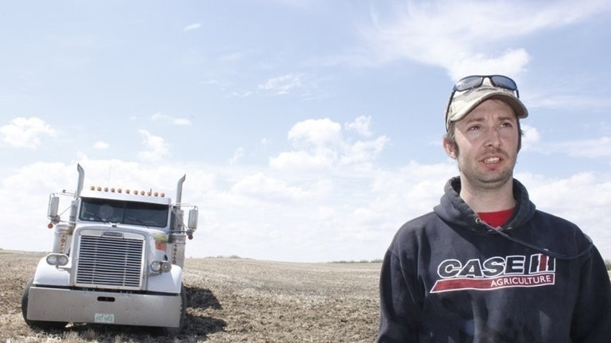 Stuart Leonard, 34, takes a break from seeding to explain how Chinese-led real estate speculation has made it harder for young local farmers to buy land in Ogema, Saskatchewan, on May 23, 2013.