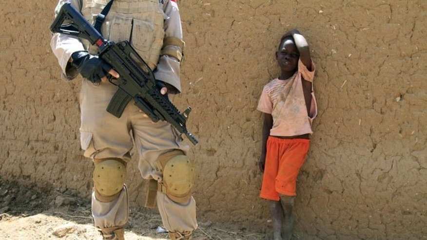 A young boy watches a United Nations peace keeper in the North Darfur state capital of El-Fasher, on June 17, 2013. Continued fighting in the region over the past seven months has created many new arrivals at camps for displaced people.
