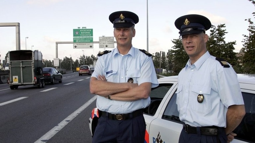 Two Dutch traffic policemen stand by their vehicle in Cestas, on August 27, 2004. Dutch police have briefly detained two brothers aged five and seven who crashed a car after a mile-long joyride.