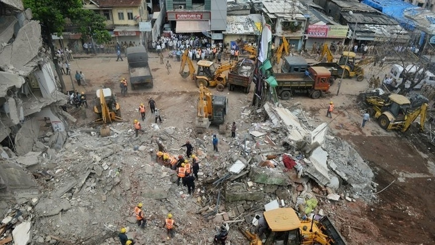 Indian rescue officials clear the rubble and debris at the site of a building collapse in Mumbai on June 11, 2013. A four-storey building collapsed in Mumbai Saturday, killing five people in the second such incident in as many days and underlining shoddy construction practices in the financial capital of the country.