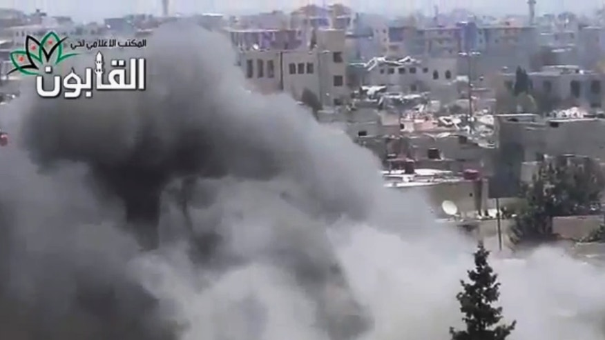 June 21, 2013: This image made from amateur video released by Ugarit News, which has been authenticated based on its contents and other AP reporting, shows smoke rises in Damascus, Syria.
