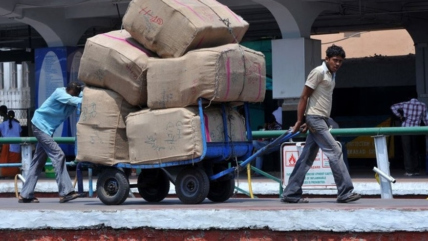 Indian railway labourers move cargo at a railway station in Hyderabad on March 13, 2012. US business leaders have urged the Obama administration to threaten retaliation against India over what they charge are unfair trading practices