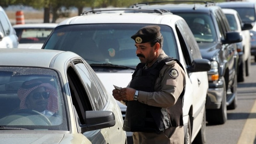 A Saudi policeman checks the ID card of a driver at a checkpoint in the mostly Shiite Qatif region of Eastern Province on November 25, 2011. A young man died on Saturday in Saudi Arabia's restive Shiite-populated region of Qatif, police said, saying he had been found in his car after unknown gunmen opened fire at patrolmen in the area.