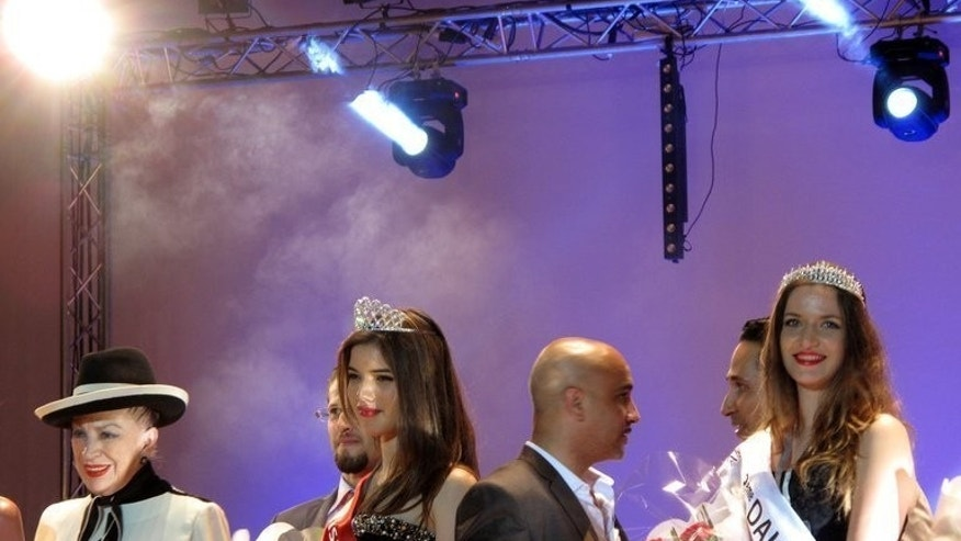 Rym Amari, Miss Algeria 2013, (C) stands with French beauty contest organiser Genevieve de Fontenay (L) and one of the runners-up at the end of the beauty pageant in the western city of Oran late on June 21, 2013. After an absence of 10 years, the Miss Algeria beauty contest was held in Oran, with 19-year-old science student Rym Amari taking the pageant honours.