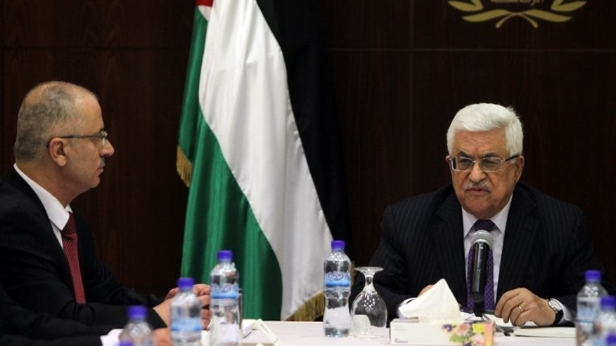 Palestinian president Mahmud Abbas (R) chairs the first meeting of the new government along with prime minister, Rami Hamdallah, in the West Bank city of Ramallah on June 6, 2013. Abbas will meet on Sunday with Hamdallah in a new bid to defuse a political crisis that prompted the premier to submit his resignation, a senior Palestinian official said.