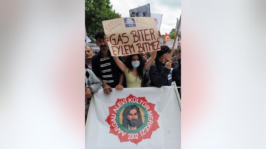 "A participant holds a sign with a picture of Recep Erdogan that reads, ""Killer"" as she takes part in a protest against the Turkish government on June 22, 2013 in Cologne, western Germany."