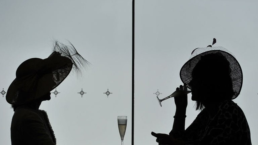 Racing enthusiasts are pictured on the fourth day of the horse racing festival at Royal Ascot in Berkshire, west of London, on June 21, 2013. Royal Ascot week ended on a sombre note on Saturday when Thomas Chippendale collapsed and died soon after passing the winning post in the Hardwicke Stakes.