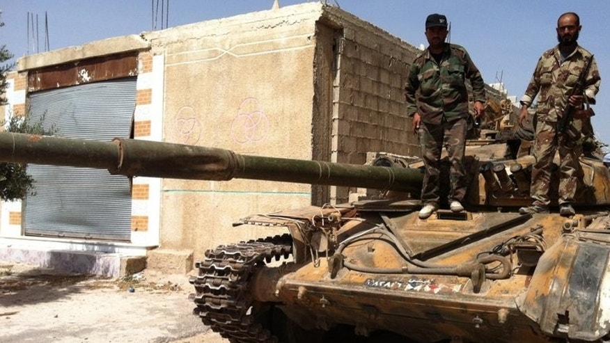 A picture taken on June 8, 2013 shows Syrian soldiers standing on a tank in the village of Buweida, in Homs province.