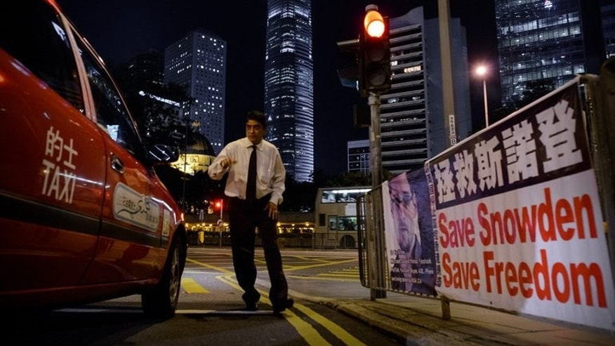 "A man crosses a street next to banner displayed in support of former US spy Edward Snowden, in Hong Kong, on June 17, 2013. The Sunday Morning Post said the 30-year-old Snowden remained ""safe"" in Hong Kong and had not been detained by police after he was charged in the United States with theft and espionage."