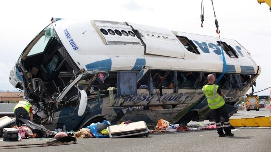 Workers tow a bus off the road after it crashed along the A8 highway, carrying about fifty Romanian nationals, on September 2, 2012, near the French city of Vidauban. Thirteen people died and 32 others were injured when a Romanian bus carrying some 46 passengers crashed in a Montenegro gorge on Sunday, Interior Minister Rasko Konjevic said.