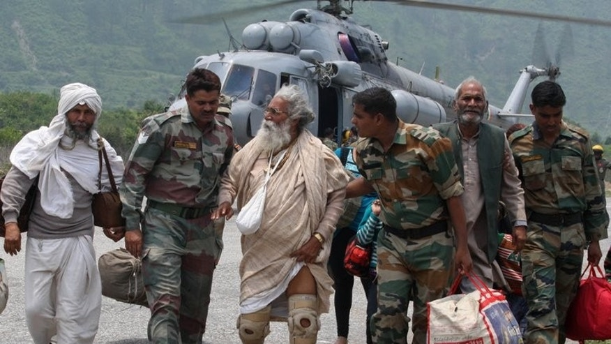 Indian defence personnel assist elderly civilians after being flown to safety, in Uttarakhand, on June 22, 2013. Bad weather hampered rescue operations in rain-ravaged northern India where up to 1,000 people are feared to have died in landslides and flash floods that have left pilgrims and tourists stranded in remote mountains without food or water.