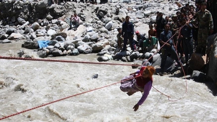 Indian military help a pilgrim cross a swollen river in Uttarakhand state on June 22, 2013. More than 20,000 people were cut off in remote areas with the full extent of the loss of life only likely to emerge after flood waters recede and rescue workers reach isolated areas, officials said.