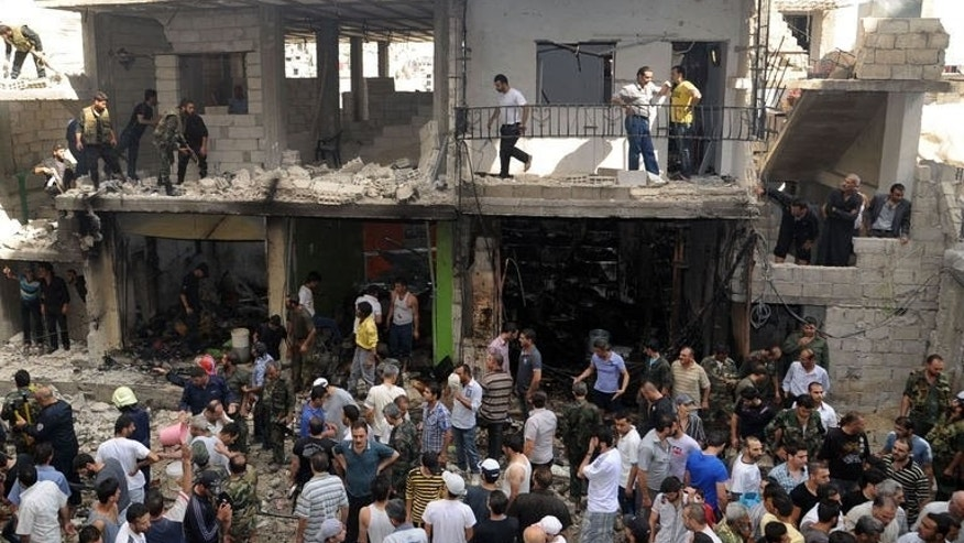 "A handout picture released by the Syrian Arab News Agency (SANA) on June 23, 2013, shows civilians and security at the scene of a bombing in the Mazzeh 86 area of Damascus. Rebel attacks in and around Damascus have killed at least 10 people, as French President Francois Hollande urged the mainstream opposition to ""retake"" areas that have fallen into jihadist hands."
