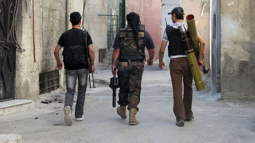 "A handout picture released by the opposition-run Shaam News Network on June 22, 2013 shows rebel fighters walking in the Syrian capital Damascus. Rebel attacks in and around Damascus have killed at least 10 people, as French President Francois Hollande urged the mainstream opposition to ""retake"" areas that have fallen into jihadist hands."