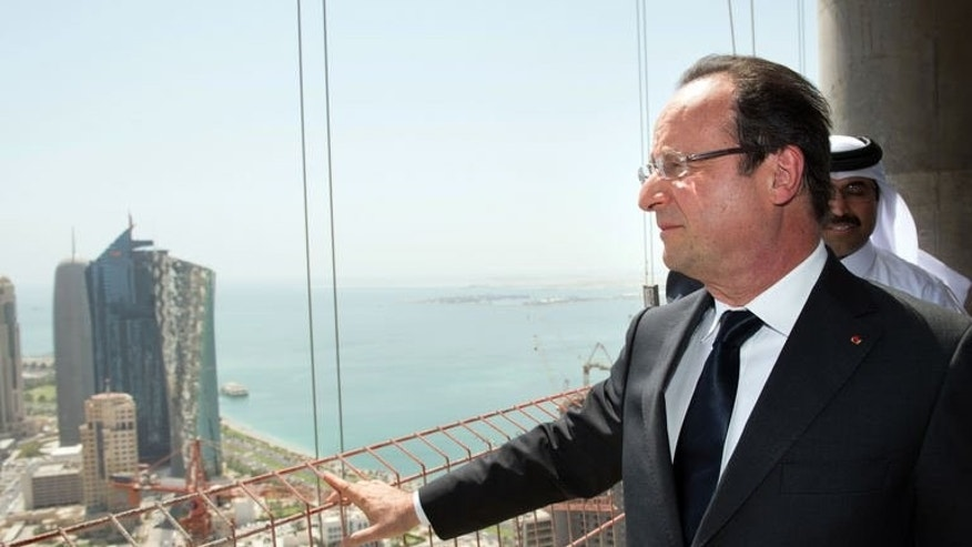 "French President Francois Hollande visits a Bouygues construction site in the Qatari capital Doha, on June 23, 2013. Hollande is on a two-day official visit to Qatar for talks on the Syrian civil war and on economic ties with the gas-rich Gulf state. Hollande says he has ""every reason to believe that eight Europeann hostages are alive"", and that Paris was ""always seeking contacts"" to free them."