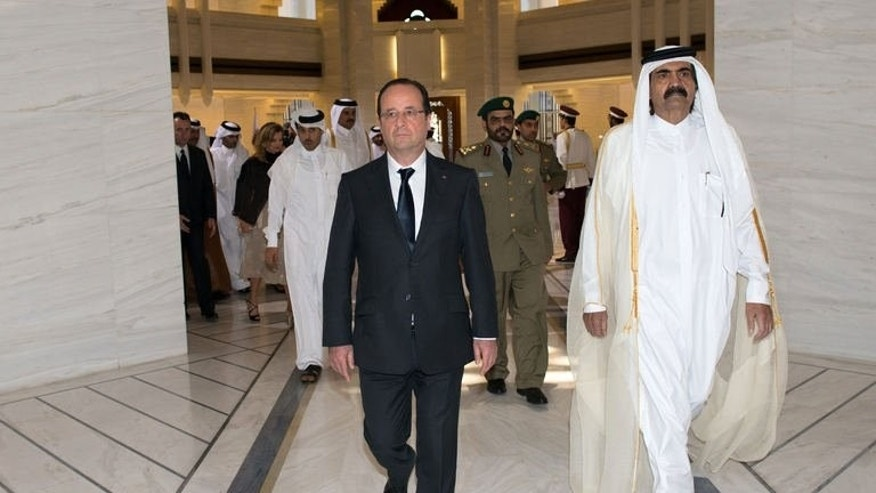 """French President Francois Hollande (left) is greeted by Qatari Emir Sheikh Hamad bin Khalifa al-Thani at the Emiri Diwan in Doha, on June 23, 2013. Hollande has urged rebels in Syria to """"retake"""" zones that have fallen into the hands of extremist Islamist groups."""